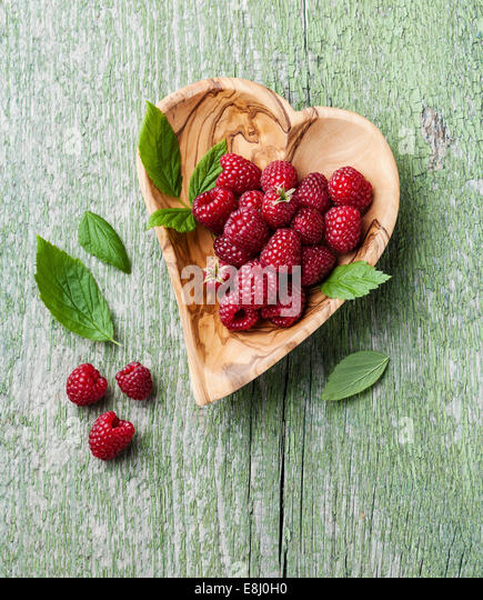 Raspberries with leaves in olive wood bowl shape of heart on green wooden background - Stock Image