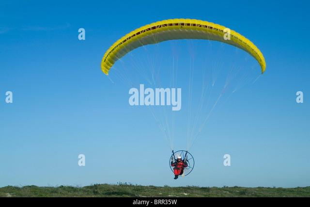 A motorized hang glider flying through the air - Stock Image