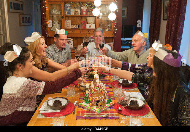 Horizontal portrait of three generations of a family enjoying Christmas lunch together round the table. - Stock-Bilder