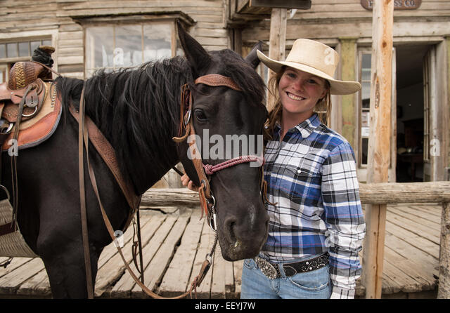 Virginia City Overland Stage employee Mariah Fredrickson waits with her horse Oakley for a stage coach tour to return - Stock Image