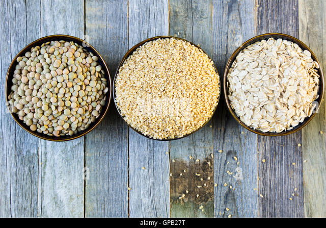 Bowls of lentils, bulgur and rolled oats in a row viewed from above on an old wooden table. - Stock Image