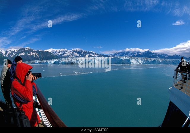 Alaska cruise ship Hubbard Glacier woman tourist red parka photographs cold ice blue glacier - Stock Image