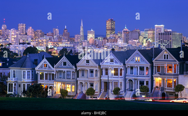 View of old Victorian houses on steiner street with financial district of city in distance San Francisco, California, - Stock Image