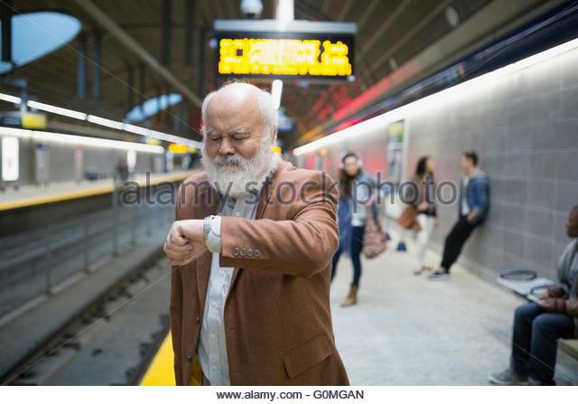 Senior man beard checking wristwatch subway station platform - Stock-Bilder