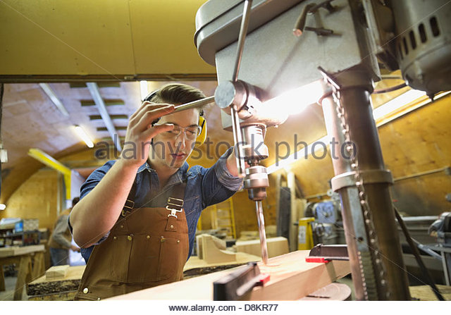 Young male carpenter using drill press on lumber - Stock Image