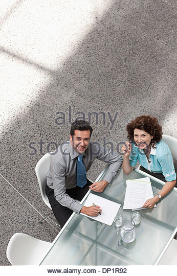 Smiling businessman and businesswoman looking up - Stock Image