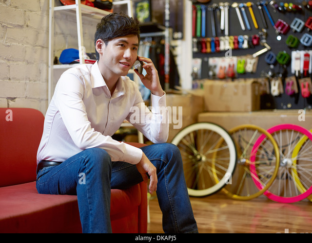 Young man sitting in bike shop on cell phone - Stock Image