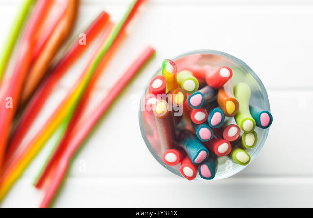 Sweet gummy sticks with different flavor. Top view of tasty candy in glass cup. - Stock Image
