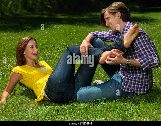 Young happy couple in their early thirties having fun in the nature on green grass. Young man tickling young woman's - Stock Image
