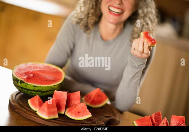 Mature woman eating watermelon in kitchen - Stock Image
