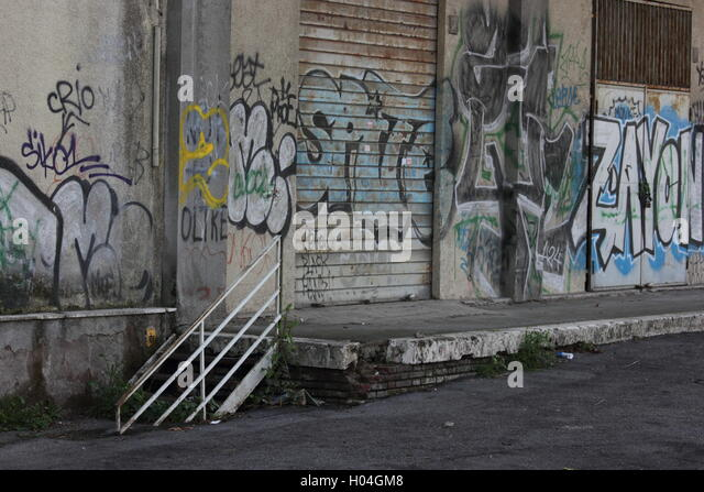 a beautifully decayed urban street alleyway with graffiti - Stock Image