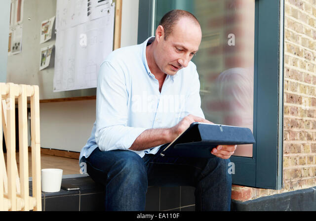 Male architect using touchscreen on digital tablet on office step - Stock Image