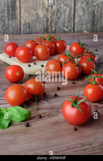 Scattered cherry tomatoes with pepper and leaves of basil on the wooden, brown table with the light wooden board. - Stock Image