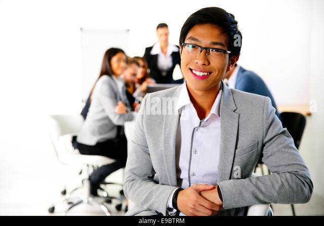 Businessman sitting on the office chair in front of business meeting - Stock Image