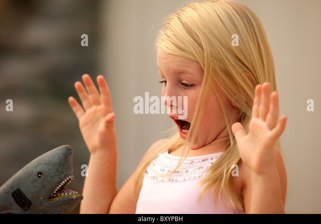 Young girl afraid of shark toy - Stock Image