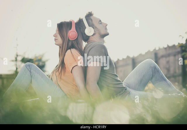 Boy and girll listening to music on headphones - Stock Image