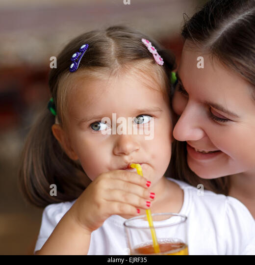 Closeup facial portrait of a little girl drinking juice through a straw next to her mother. Shallow depth of field. - Stock Image
