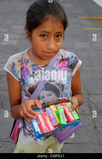 Lima Peru Plaza de Armas Hispanic indigenous girl child grade school age street vendor vending selling gum Chiclets - Stock Image
