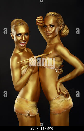 Fancy Dress Party. Couple of Women with Golden Metallic Painted Skin. Creativity - Stock Image