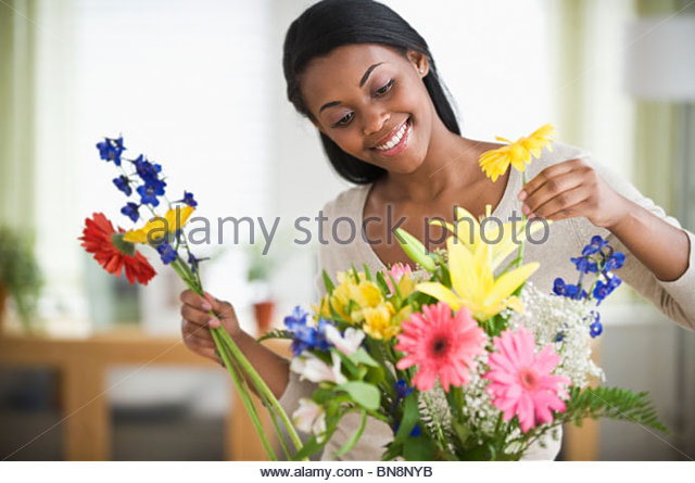 African American woman arranging flowers - Stock Image
