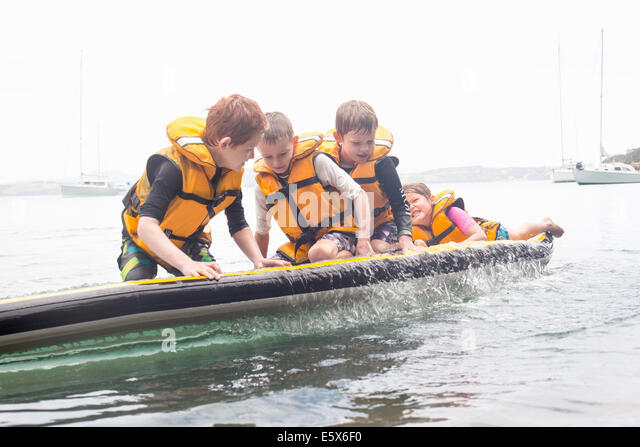 Brothers and sister about to fall from paddleboard into sea - Stock Image