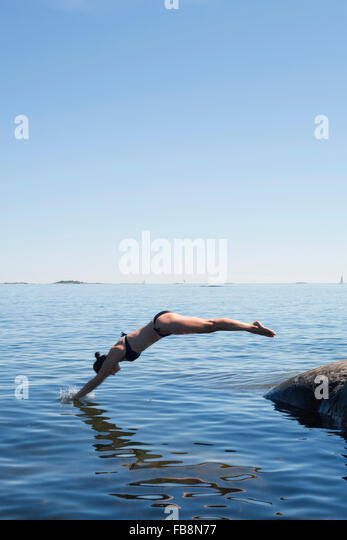 Sweden, Uppland, Runmaro, Barrskar, Woman jumping into sea - Stock Image