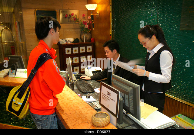 Shanghai China Dianchi Road Huangpu District Manhattan Bund Business Hotel lobby Asian woman man employee front - Stock Image