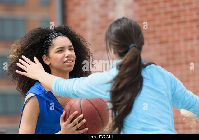 Teenage girls (14-15, 16-17) playing basketball - Stock Image