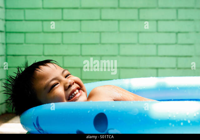 Kid in a kiddie pool - Stock Image