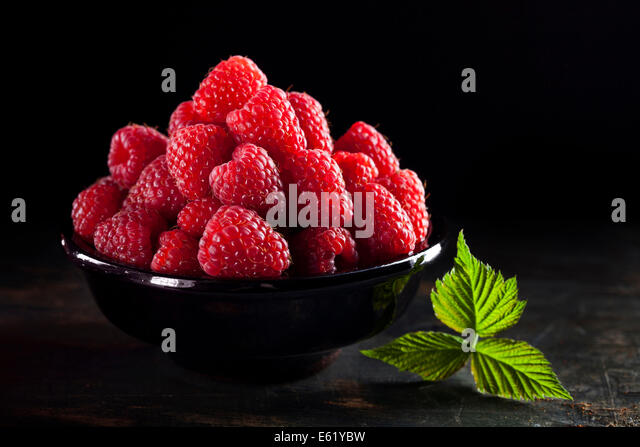 Bowl of fresh raspberry on dark background - Stock Image
