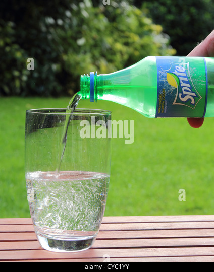 Caucasian Man pouring a drink of Sprite Brand Soft Drink into a Glass MODEL RELEASED - Stock Image