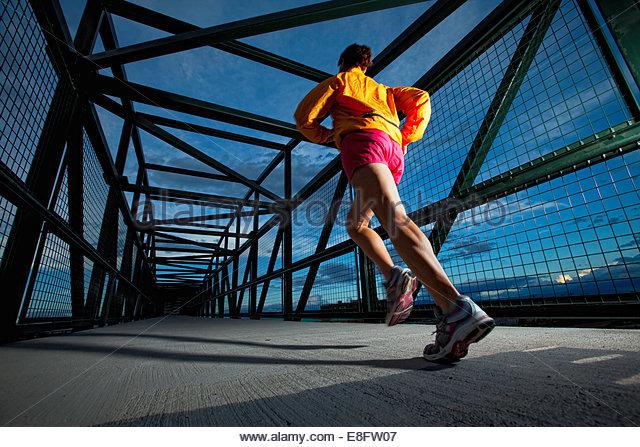 USA, Colorado, Woman jogging across bridge at dusk - Stock-Bilder