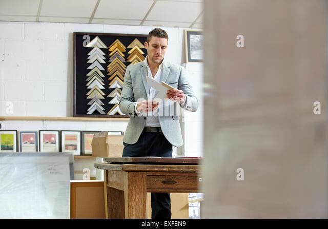 Framer selecting frame in picture framers workshop - Stock Image
