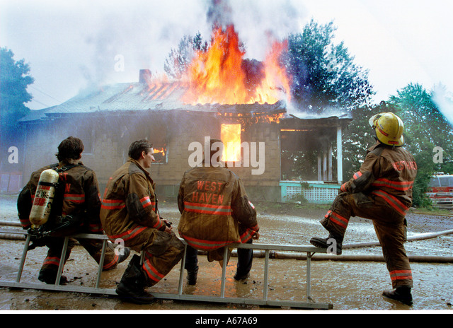 Humor Firefighters watching a house burn as they relax - Stock Image