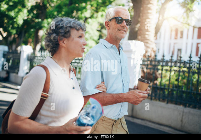 Senior man and woman walking in the city. Mature tourist roaming in a town during their vacation. - Stock Image