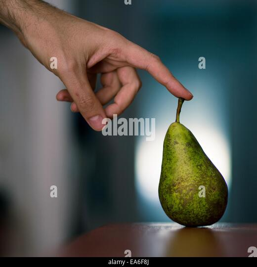 Spain, Man touching pear - Stock Image