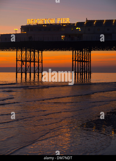 Brighton Pier sunset at low tide - Stock Image