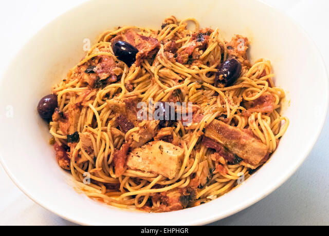 Spaghetti with tuna, bacon, olives, and tomato sauce in a white bowl ...