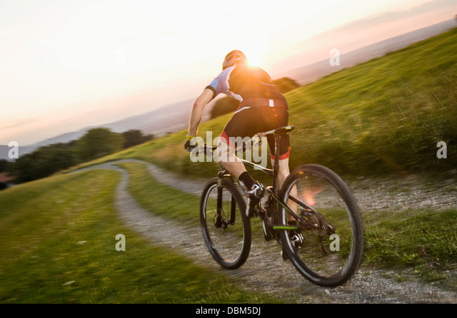 Mountain biker riding on a trail at sunset, Samerberg, Germany - Stock Image