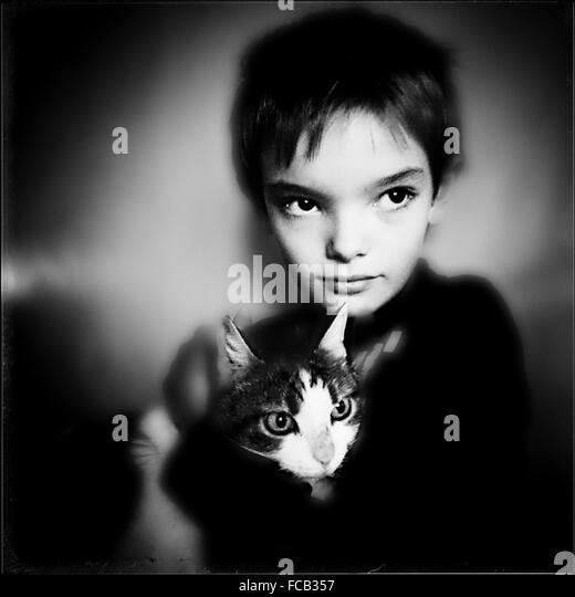 Portrait Of Boy Holding Cat - Stock Image