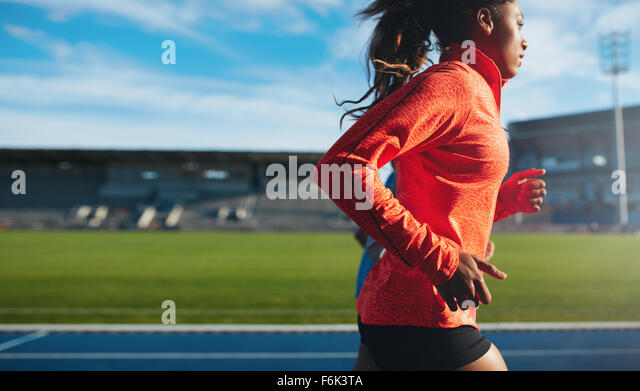 Side view of fit young woman running. African female athlete training on race track at athletics stadium. - Stock Image
