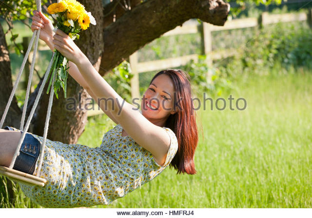 Portrait happy brunette woman swinging on tree swing with flower bouquet in sunny summer rural yard - Stock-Bilder