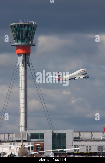 British Airways Boeing 747 taking off in the background of London Heathrow control tower. - Stock Image