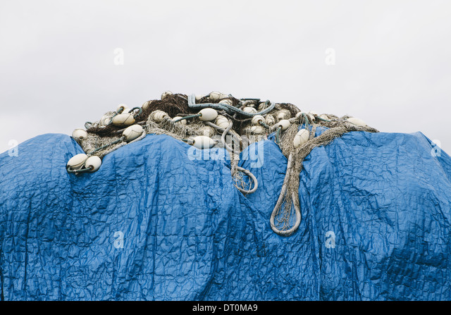 Seattle Washington USA blue tarpaulin covering commercial fishing nets - Stock Image