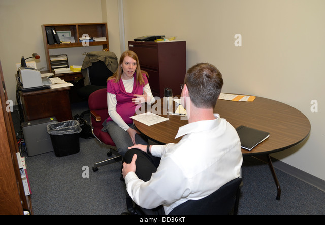 Inmate talking to case worker in prison as part of the intake process. - Stock Image