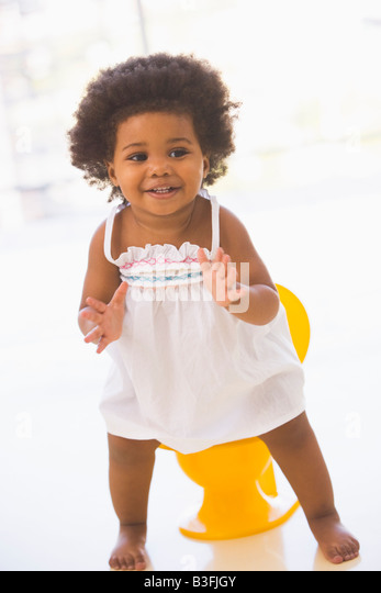 Baby indoors going on potty smiling - Stock Image