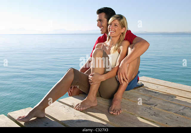 Happy couple on a jetty by the sea - Stock Image