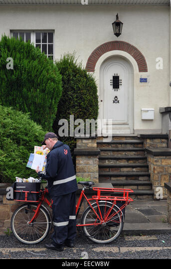 Belgian Postman at work with its business cycle - Stock Image