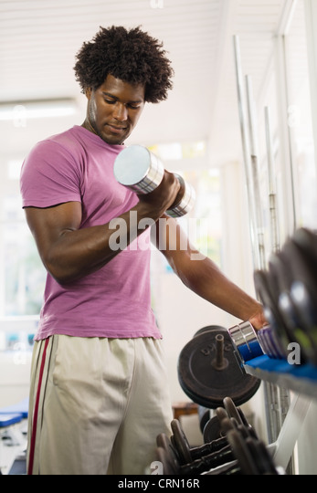 Sport and fun, young african american male athlete taking weights from shelf in fitness club - Stock Image