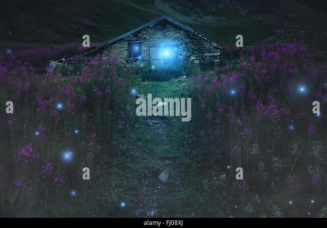 Mysterious mountain cabin surrounded by will o wisp. Fantasy and halloween - Stock-Bilder